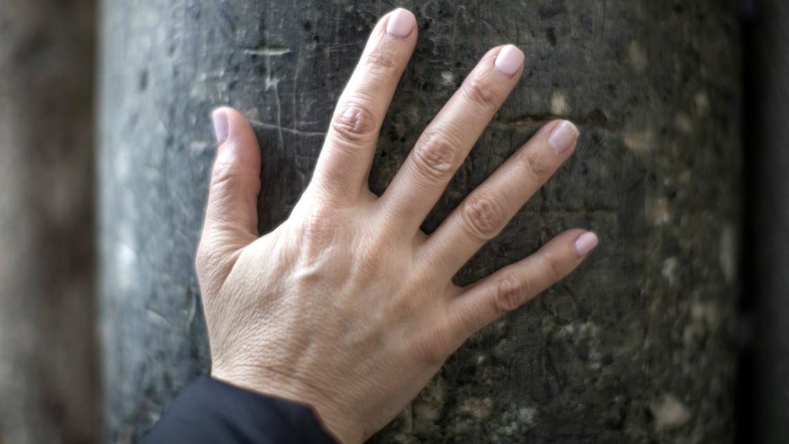 kezét a hideg vörös foltoktól